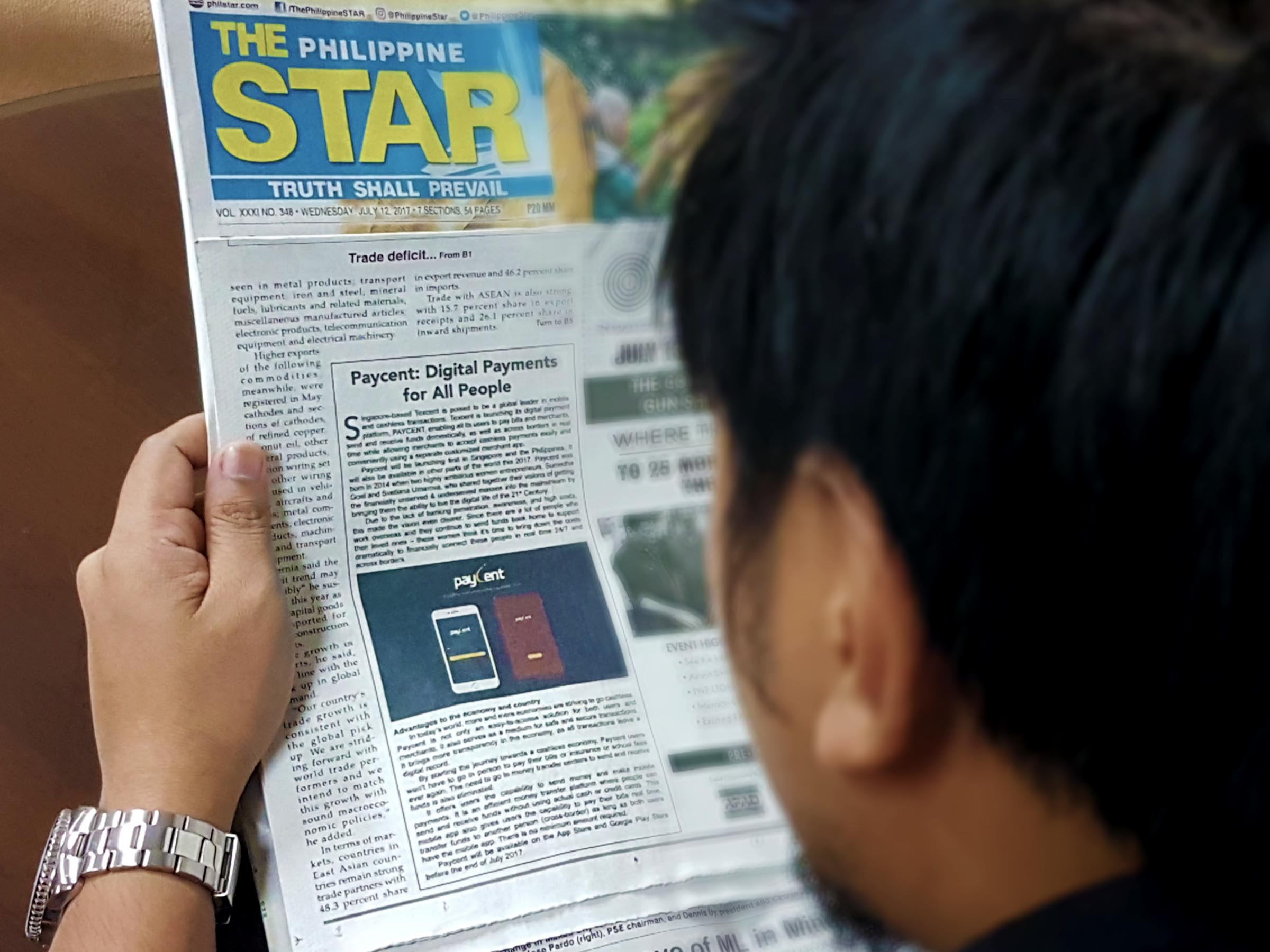 Man reading about Paycent featured in the newspaper.